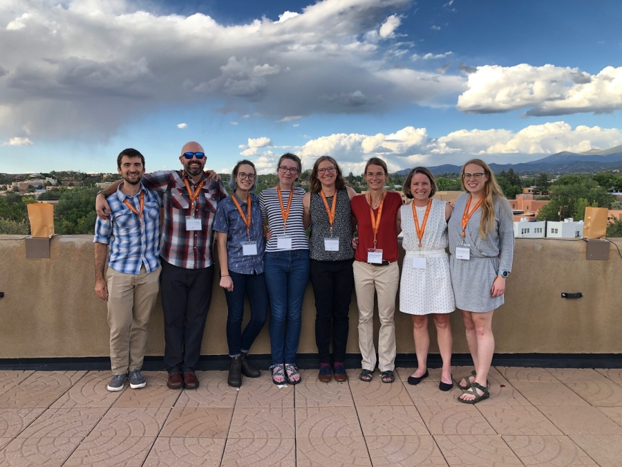 eight geologists standing on a rooftop patio with Santa Fe in the background